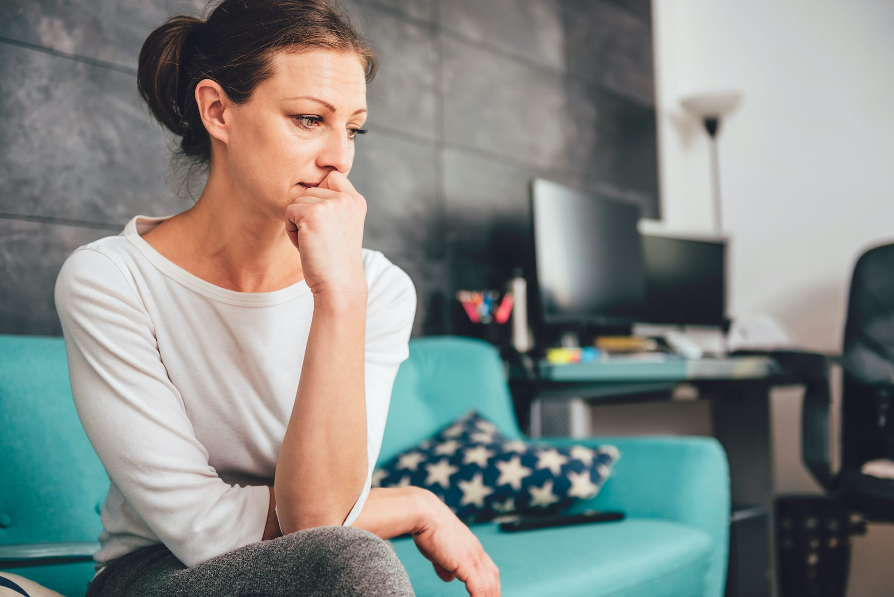 Worried woman sitting on a couch