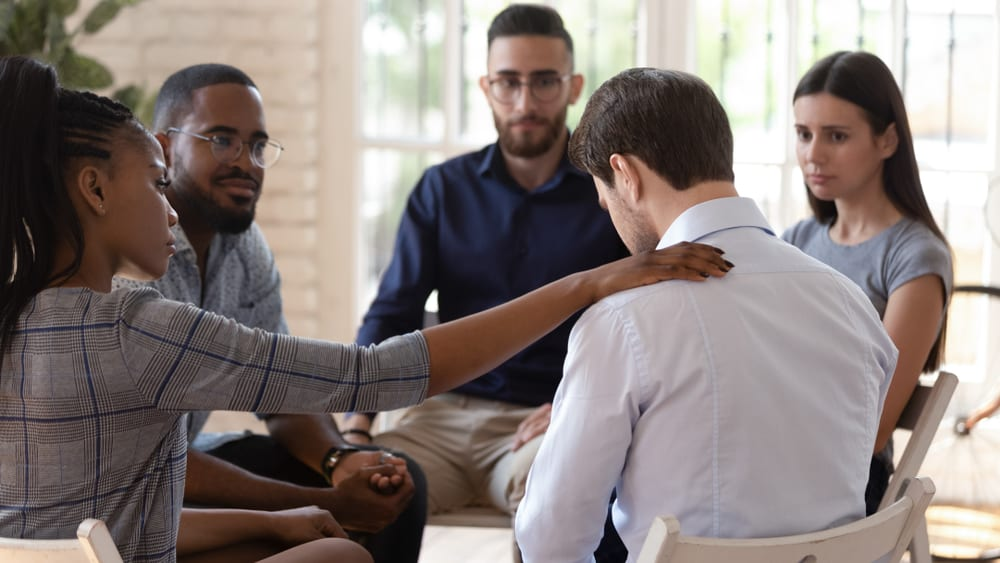 Man being comforted by his peers in his group meeting in Westmoreland County, PA.
