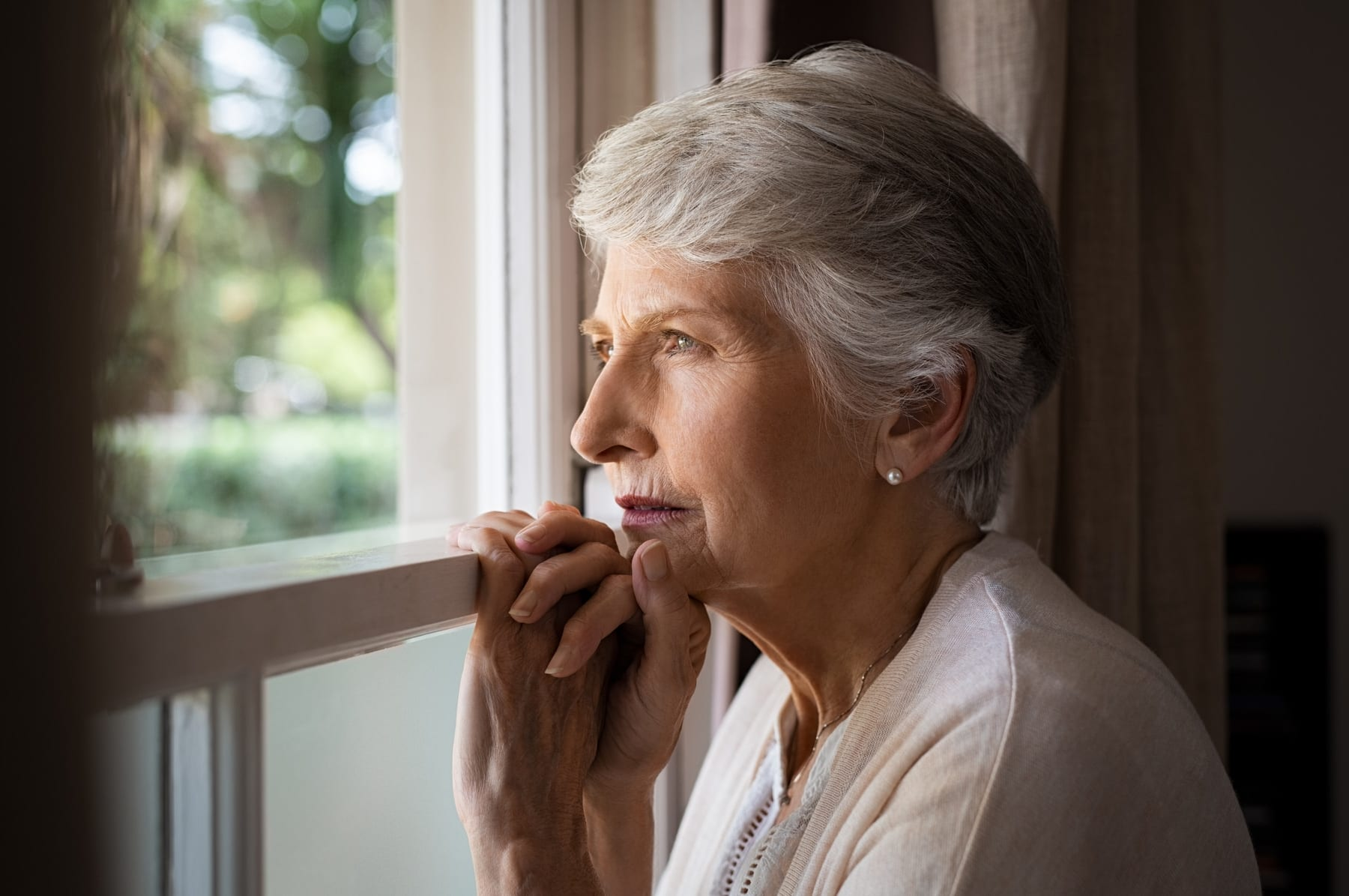 Older woman looking sadly out a window